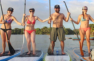 people standing on paddleboards